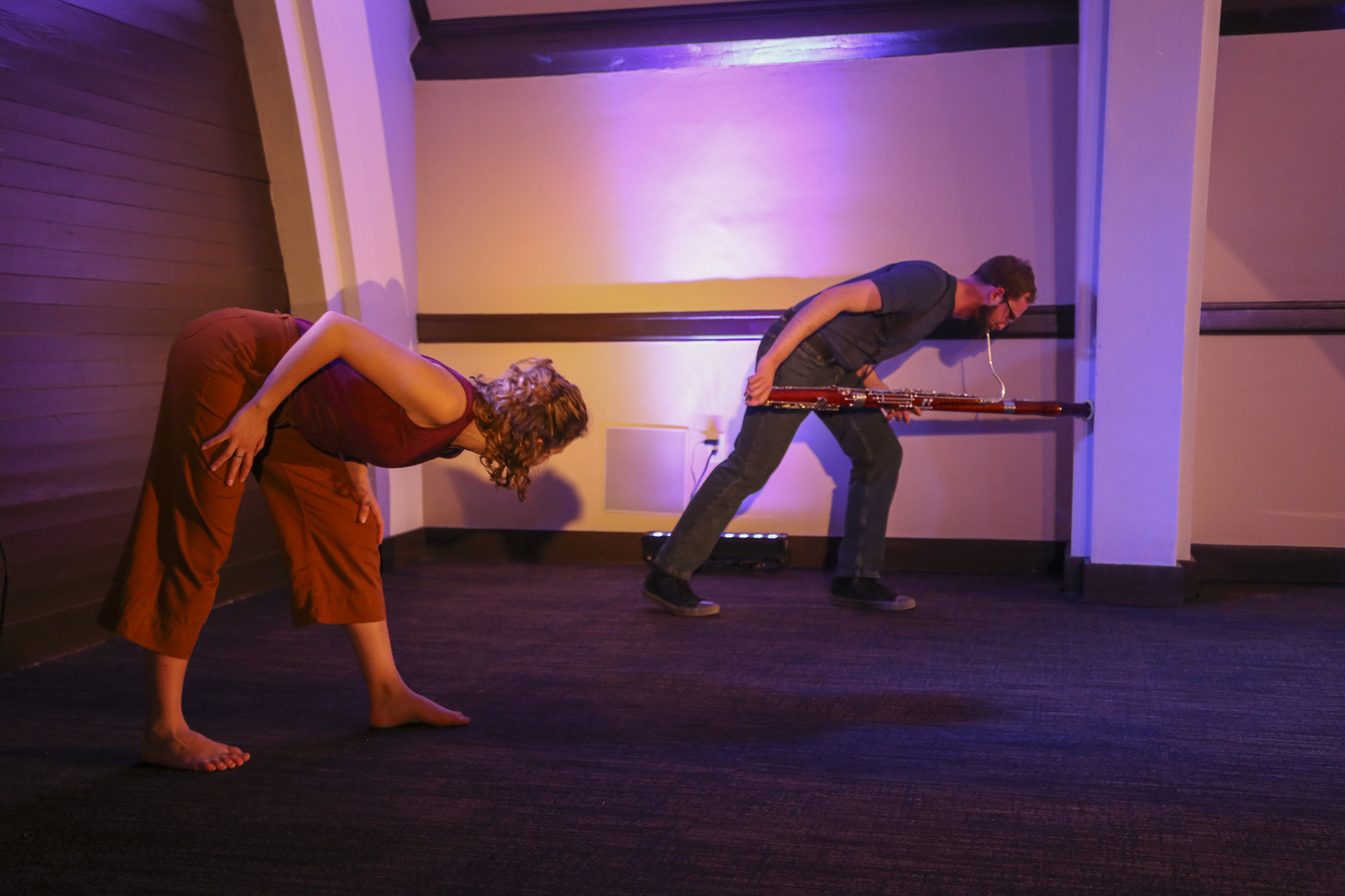 Two people bend at the hips towards the right. The woman closest to the camera is watches the other person. The person bending in the back is holding a bassoon parallel to the floor and is pushing it against the wall while playing it. They are wearing shades of dark blue, while the woman wears shades of orange and red. The room is cast in a dim pink light.