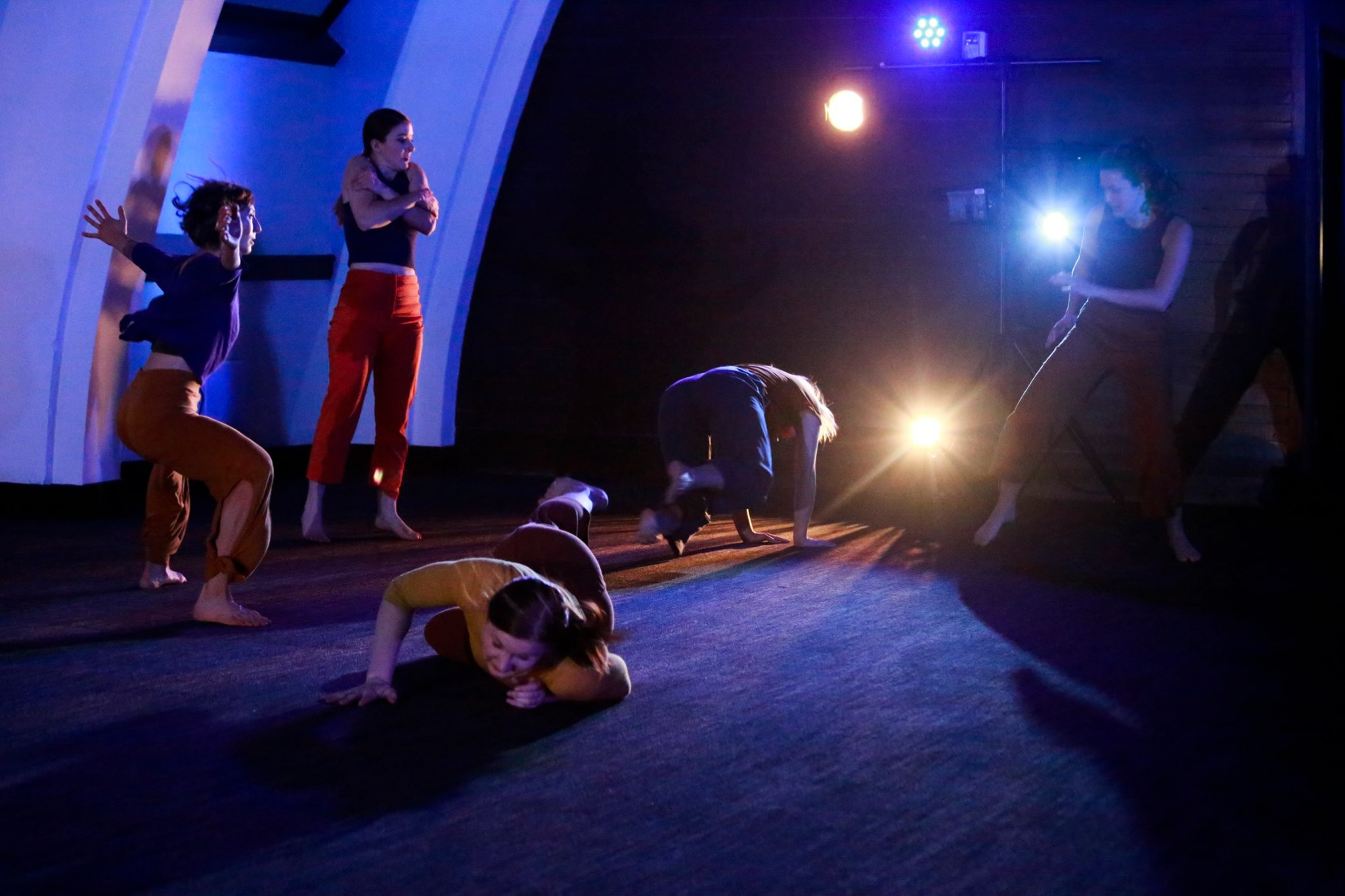 Five women are in mid-action. The room is dark, cast in shades of blue and purple. One woman has her arms flung wide and is crouching. Another is falling to the ground. A third woman is pushing into the ground with her hands, holding herself up. The fourth woman is taking a power stance, her legs spread wide and rigid, as if to do a martial arts move. The fifth woman stands tall, her hands tightly clenched on her upper arms.