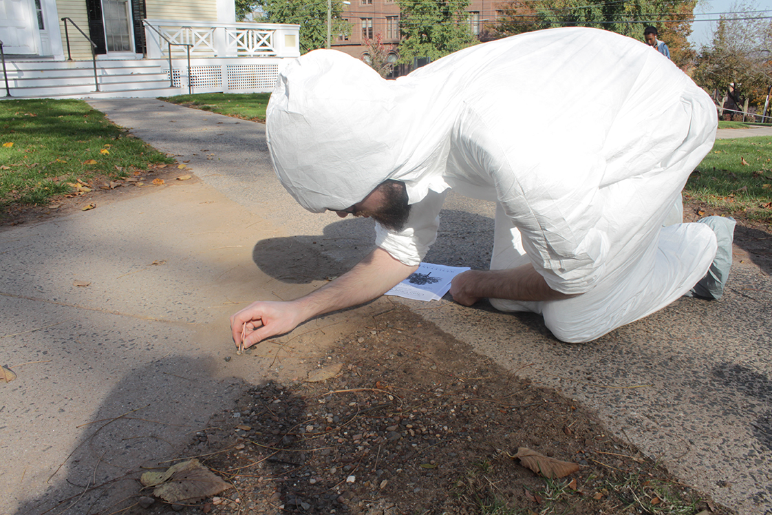 Warren, in white coveralls, is kneeling on the ground, using tweezers to remove tiny pebbles from the sidewalk. A stack of flyers sits by his knee.