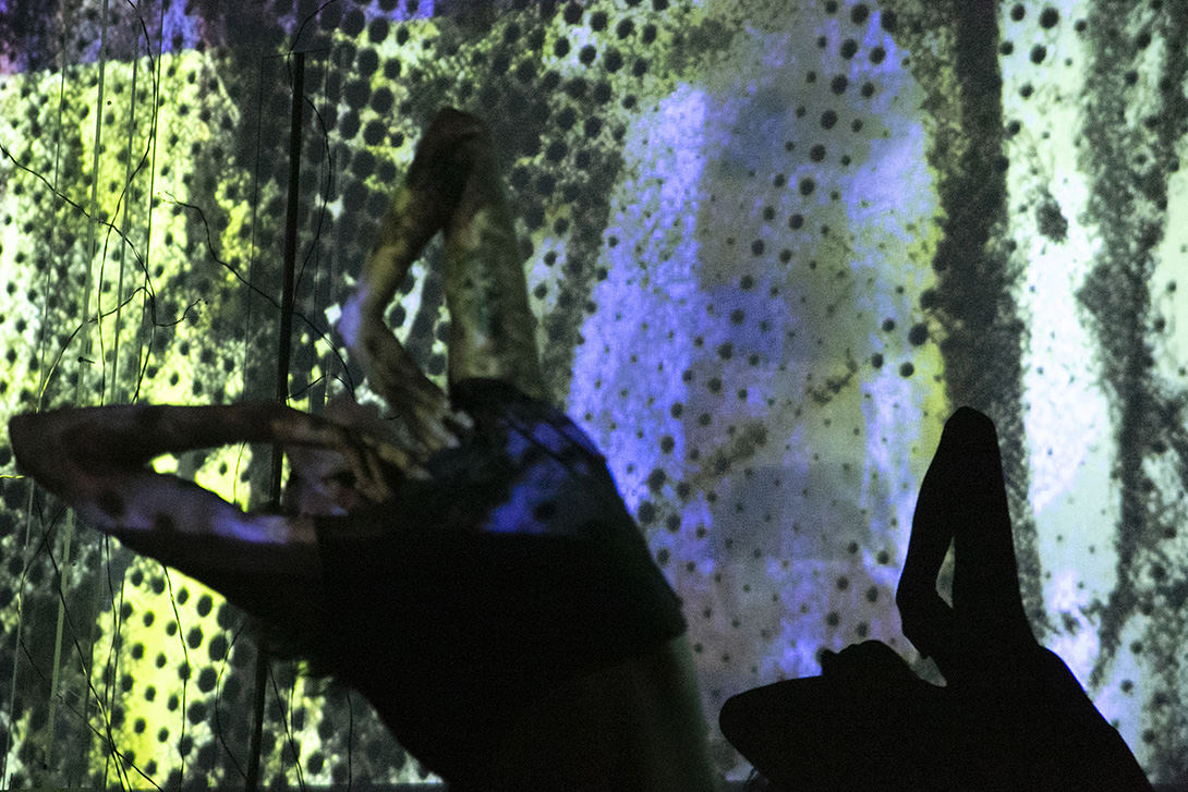 Mauriah Kraker, back arched and arms raised above her head, bent with sharp angles at each elbow, is projected upon. Yellow-green and gray-blue light and black spots are in the background. Wires from the sculptures are seen on the left of the photo.