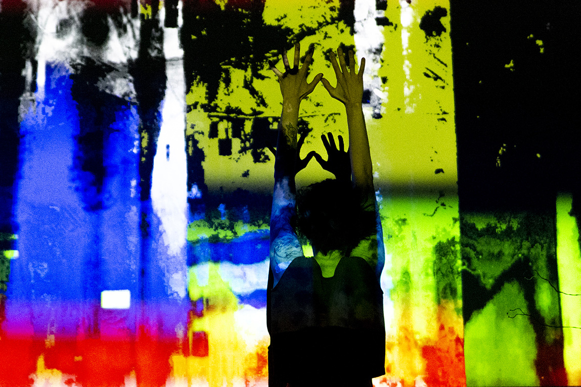 Mauriah Kraker stands straight, her arms thrust above her head, against the projection screen. Blue, yellow, red, and green are projected on the wall, as well as lines of black and white.