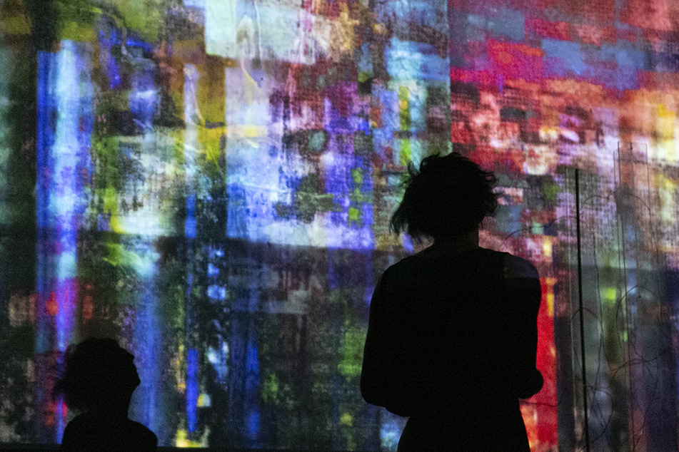 Mauriah Kraker is silhouetted against the projection screen, which is impressionistically dappled with reds, blues, greens, and purples.